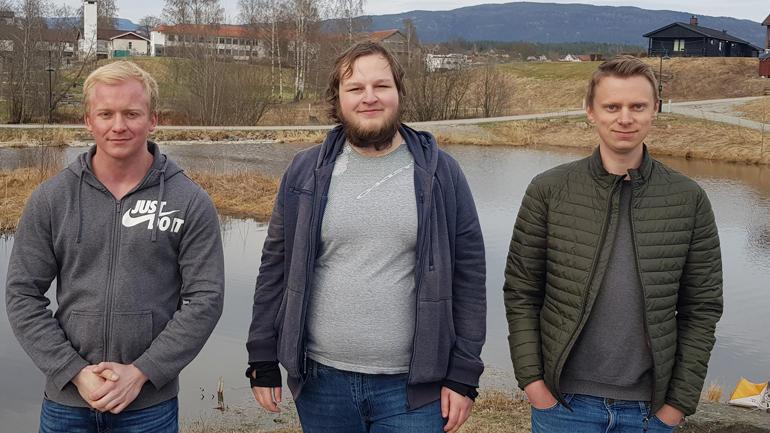 Emil, Andre og Torstein står oppstilt på rekke utendørs og ser i kamera. Halvprofil.