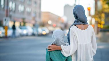 Mor og datter iført hijab poserer med ryggen mot kamera foran et urbant miljø. Foto