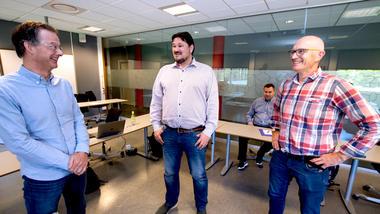 Tor Erik Jensen (til venstre), prosjektleder Christian Hovden og universitetslektor Paul Nikolai Smit stående på rekke i møterommet og ser på hverandre og smiler.