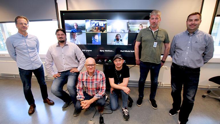 Alle nevnt i bildeteksten oppstilt foran stor TV med bilde av Zoom og alle observatørene.
