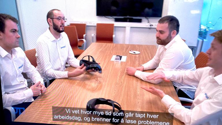 Bilde av fire av studentene i panopticXR SB sittende i hvite skjorter rundt et bord og snakker til hveradnre og smartbrillene liggende foran på bordet.
