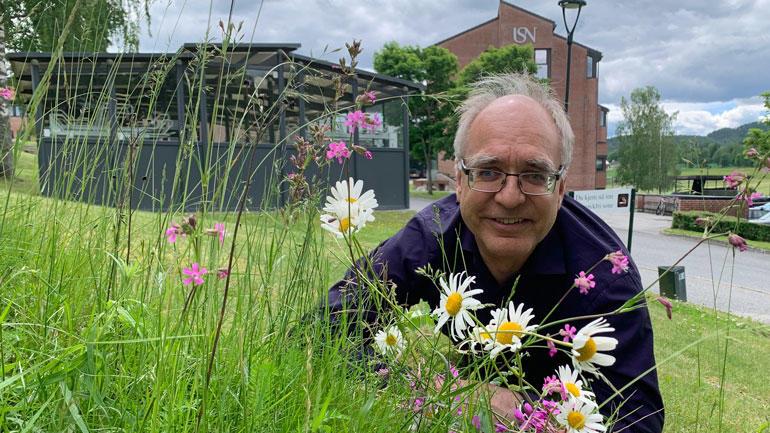 Bilde av Herleik Baklid i en blomsetereng foran universitetsbygget i Bø.
