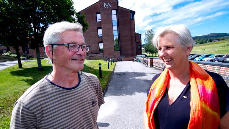 Nærbilde av Espen Lydersen og Annettet Bischoff som ser på hverandre utenfor USN campus Bø i strålende sol