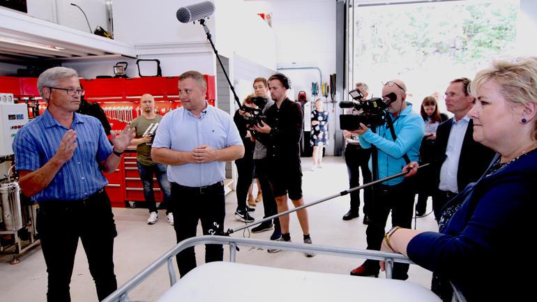 Erna Solberg hos MSG Cleaning Systems med en haug presse og Espen Lydersen og grunder Svein Gunnar Mæland som snakker
