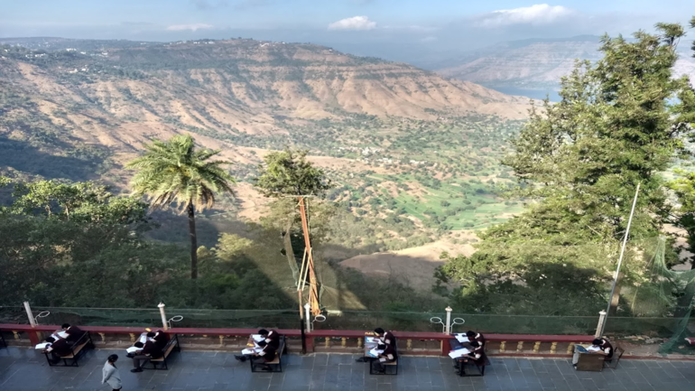 Indian schoolchildren have outdoor school exams with a stunning view over a natural landscape