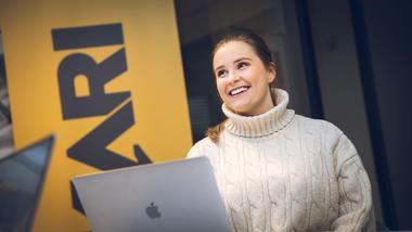 Portrett av Pia som smiler med hode på skakke og siter foran en laptop. Ser til venstre