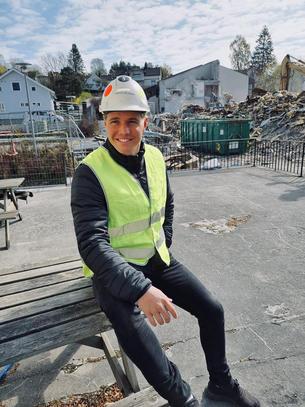 Harlad Helgesen sittene på en en haug planker på industriplass iført hjelp og gulk vest smilende til kamera.