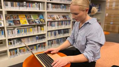 student sitter og jobber på en bærbar datamaskin i et biblioteklandskap