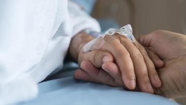 Syk person blir holdt i hånden.