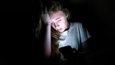 forgrått ung jente ser på en mobilskjerm