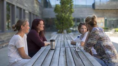 Fire studenter  sitter rundt et bord utendørs og snakker med hverandre og med termokoppen foran seg  i Kristinias Hage ved campus Vetfsold Studenter
