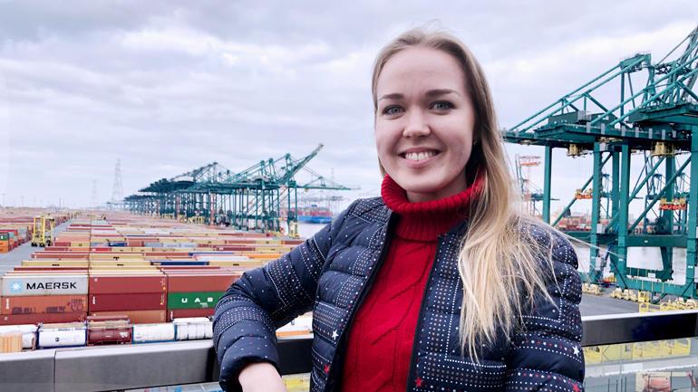 Mariia i rød høyhalsa genser og dunjakke, langtr, lyst hår smiler med tenner til kamera foran et havnemiljø.