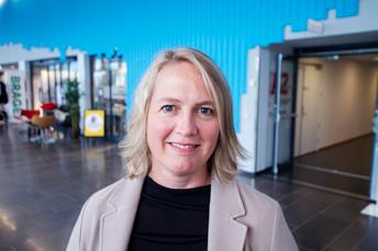 Portrett av Vibeke med lyst, halvakngt jhår uten pannelugg. Smiler til kamera og viser litt tenner. Blå vegg i bakgrunnen på campus Vestfold.