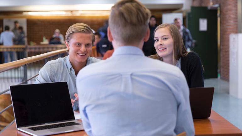 Tre studenter som studerer og diskuterer.