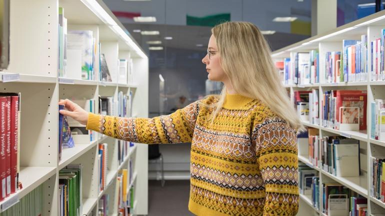 Karoline Heien velger en bok på bilbioteket campus Drammen.