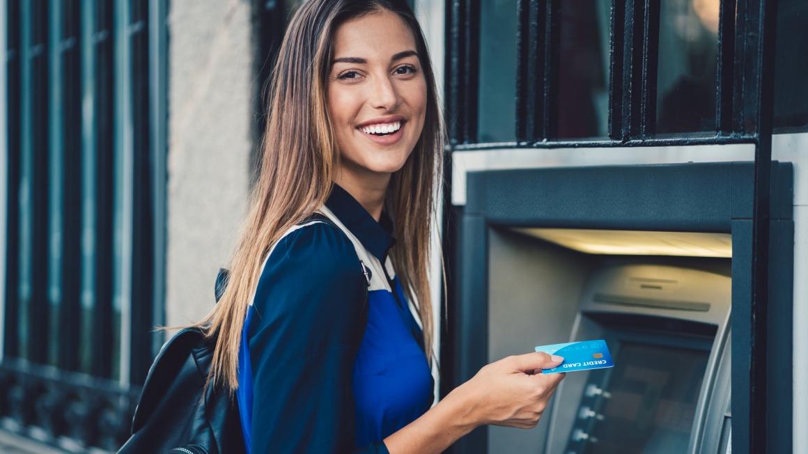 Student som tar ut penger i minibanken