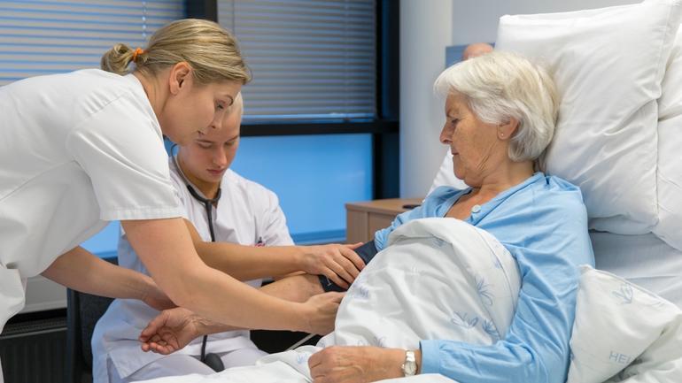 To sykepleie studenter som pleier en eldre dame