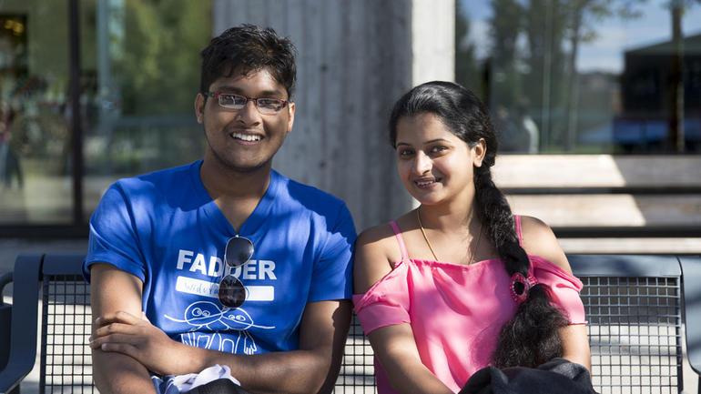 To internasjonale studenter - en gutt og en jente - sitter på en benk og smiler til kamera.