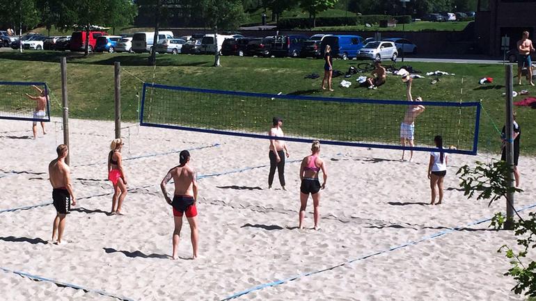 Studenter i aktivitet på sandvollyeballbanen i Bø. Sommertid