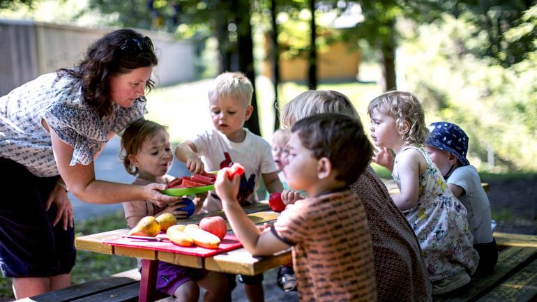 Barnehagebarn i spisepause ute med en kvinnelig barnehageansatt som hjelper. Illustrasjonsbilde