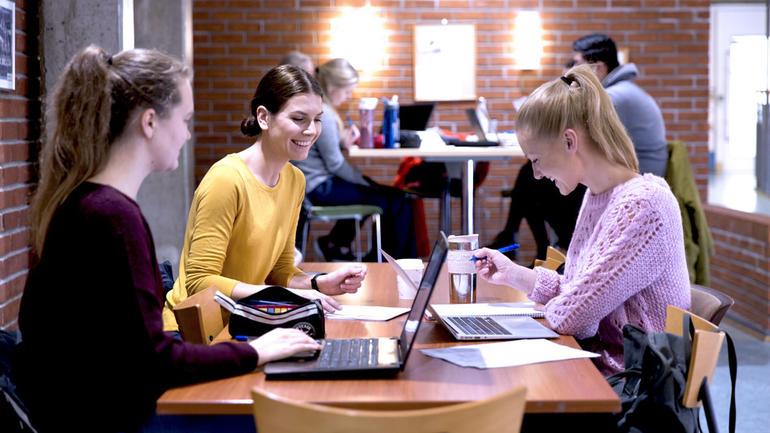 Illustrasjonsbilde av tre kvinnelige studenter som sitter rundt et bord med bøker.