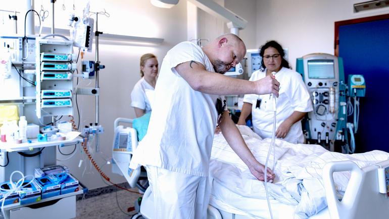 Mannlig sykepleierstudent står over pasientsenga og jobber med slanger og to kvinnelige sykepleierstudenter følger med i bakgrunnen.