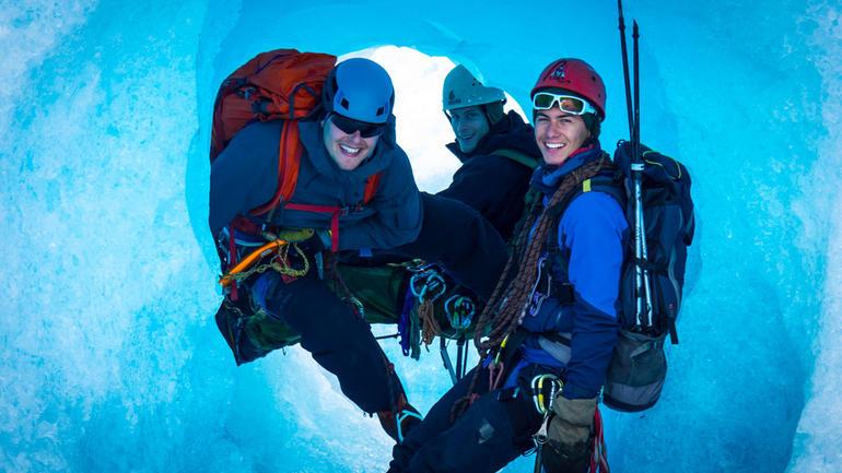 Illustrasjonsfoto til friluftstliv. Tre studenter smiler til kamera i en snøhule  med ryggsekker og hjelm.