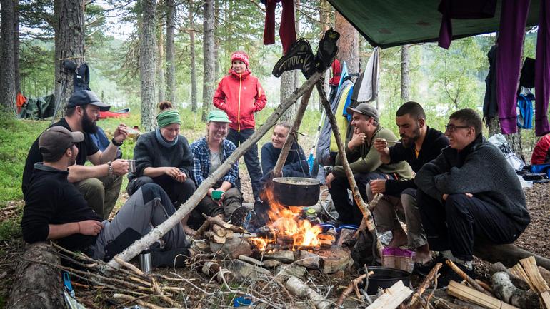 Illustrasjonsfoto til friluftsliv. En gjeng studenter ute i naturen  som koser seg med å lage mat over bål og med teltduk over leirplassen.