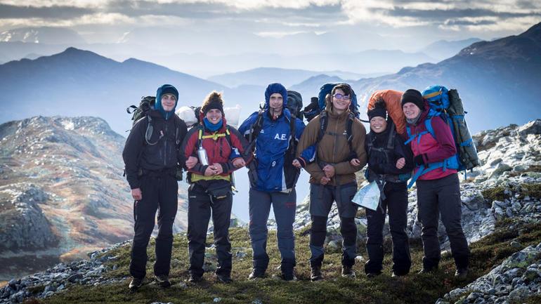 Friluftslivstudenter på rekke og rad oppe på en fjelltopp, smilende til kamera.