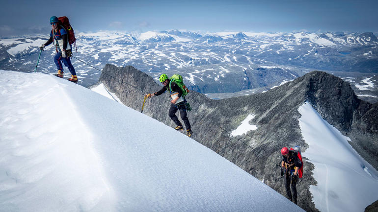 Tre mennesker på litt avstand i en bratt snødekt fjellside med klatretau og fullt utstyr. Illustrasjonsbilde