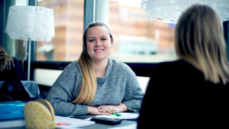Illustrasjonsbilde av en kvinnelig student som sitter ved et bord ute i aulaen og smiler til kamera med blokk og penn foran seg.