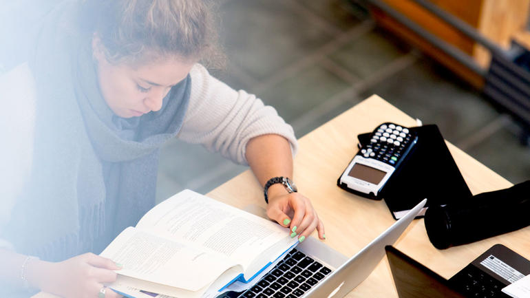 Illustrasjonsbilde av en kvinnelig student sittende foran pulten med nesa i boka foran laptopen.