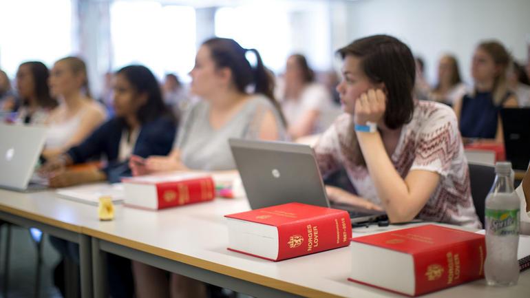 Jusstudier illustrasjon med tre Norges lover-bøkeri sentrum og studenter i forelesning i bakgrunnen