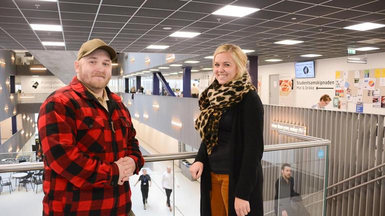 Dataingeniørstudent Gregg Roland Schneider står inne på campus KOngsberg i trappeoppgang sammen med instituttnestleder Mari Lange og smiler til kamera.