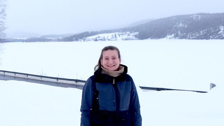 Ingrid Gormstad står rett opp og ned ute i snølandskap og smiler i kamera.