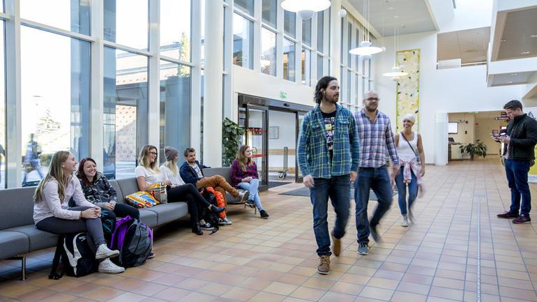 Studenter sitter og vandrer rett innenfor hovedinngangen på campus Bø