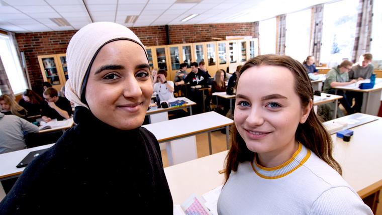Nærbilde av Fizzah og Ann-Victorie som står foran klassen og smiler til kamera.