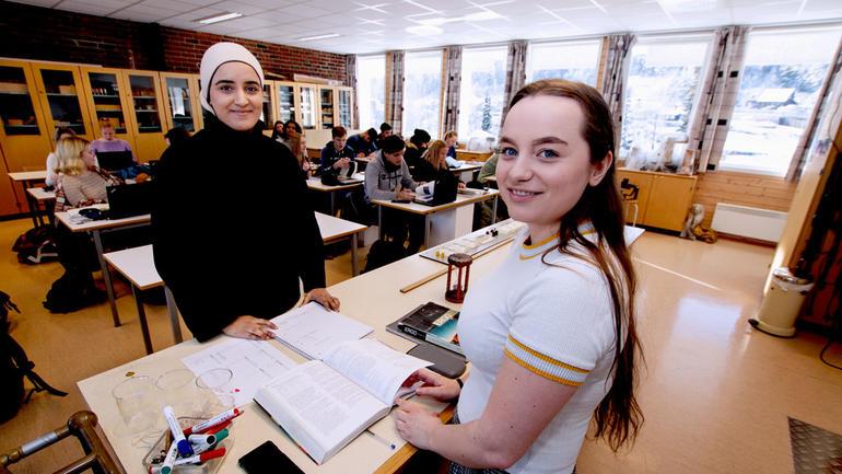 Fizzah og Ann-Victore står rundt kateter med klassen i bakgrunnen og smiler til kamera.