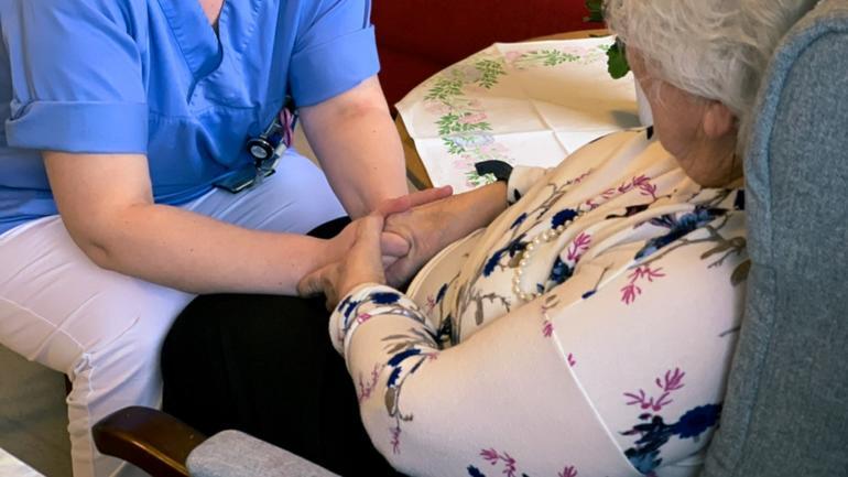 Ragnhild Bjerknes Bærug i kommunikasjon med en eldre pasient - studerer maste ri geriatri