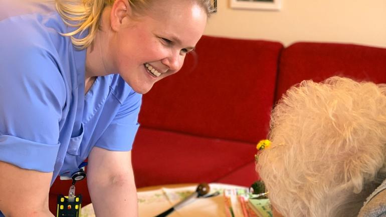Ragnhild Bjerknes Bærug i samtale med eldre pasient.