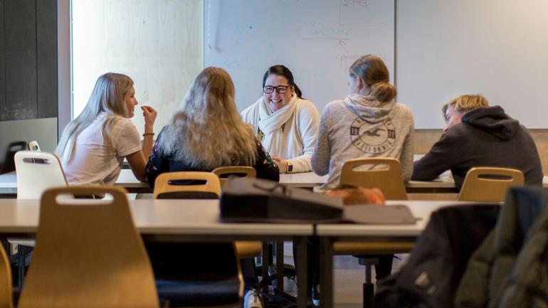 En gruppe med unge elever og student ved bord. Foto